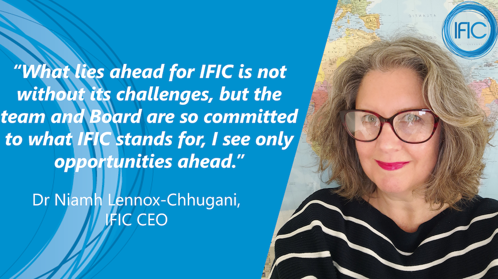 Photograph of Dr. Niamh Lennox-Chhugani standing in front of a world map, next to the text: What lies ahead for IFIC is not without its challenges, but the team and board are so committed to stands for, I see only opportunities ahead